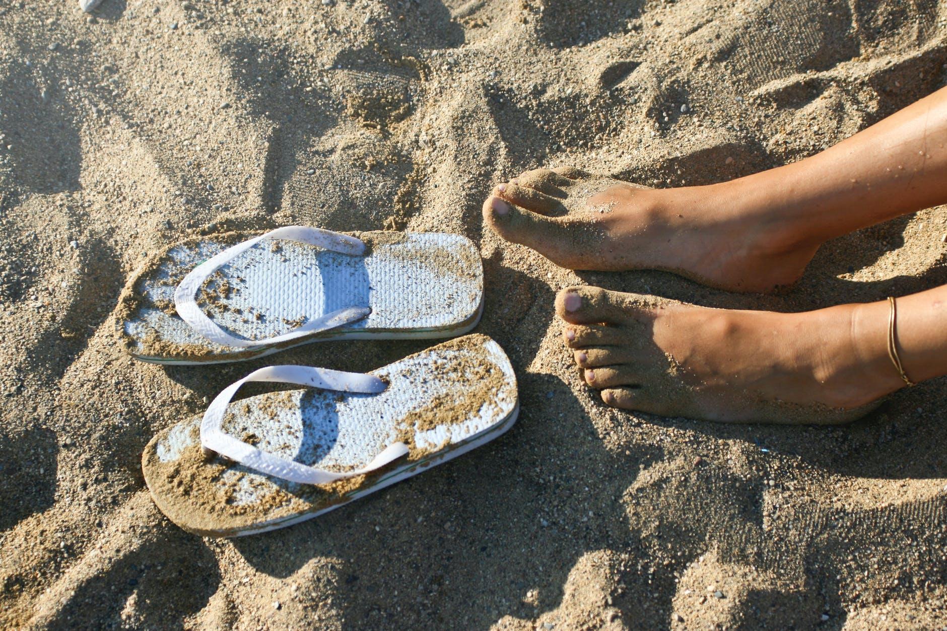 photography of a girl s feet near flip flops