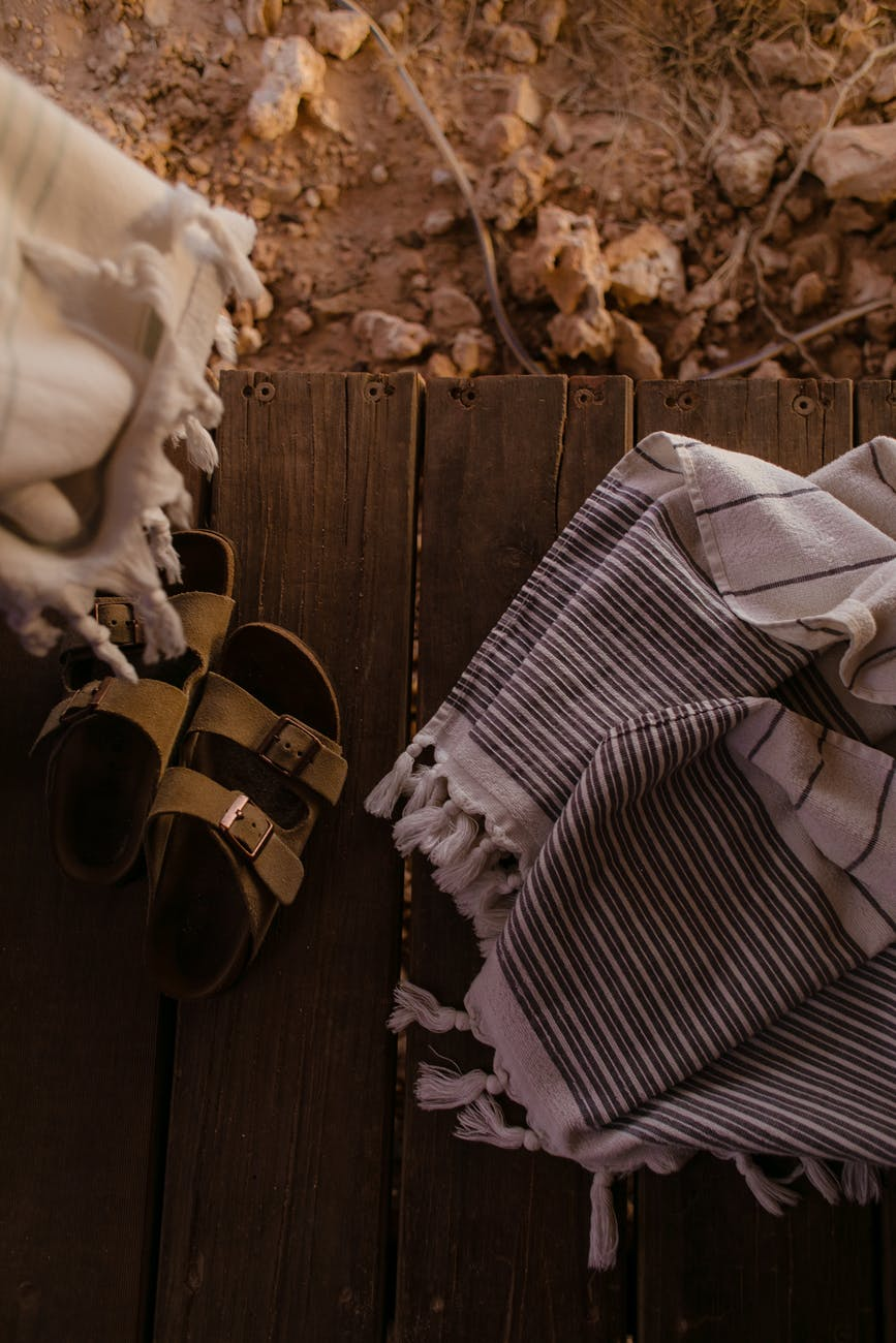 textiles and sandals on wooden surface in daytime