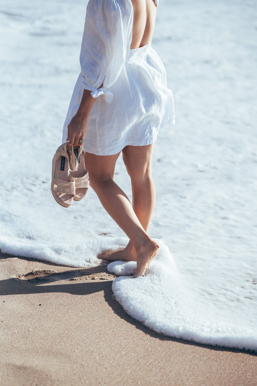 barefoot woman in white clothes walking in foamy sea